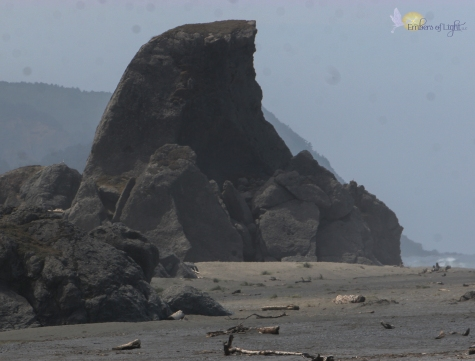 Rising out of a sandy beach are large boulders. One towers over the rest in a shark-tooth design. The side facing the ocean is sharp and jagged. The side away from the ocean is more gentle and sloping.