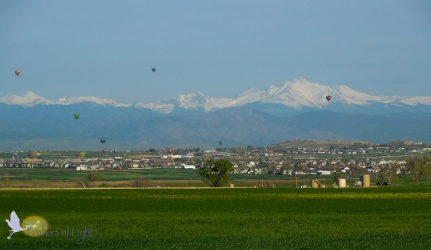 Six brightly colored balloons rise above the plains. Behind them, the Rocky Mountains and Longs Peak are easy to see. The foothills are covered in brush, but the large peaks behind are still covered in snow. A grassy field is in the foreground and urban sprawl between the fields and the foothills.