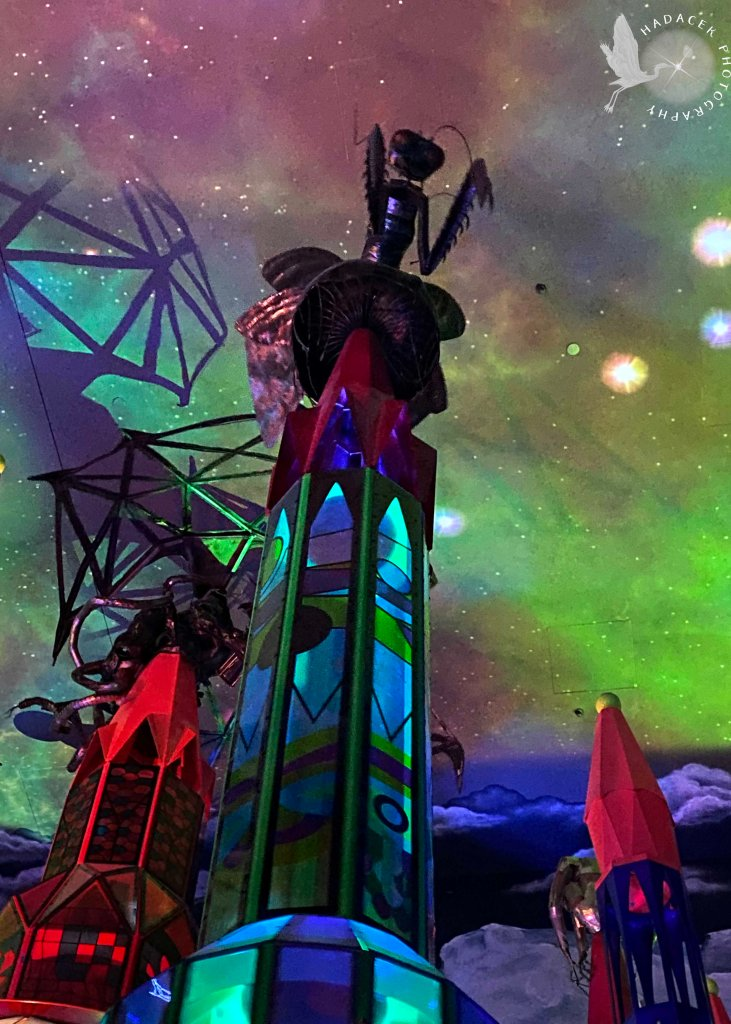 Colorful spires reach up to a space-like sky. Atop the nearest spire is a statue of a praying mantis.