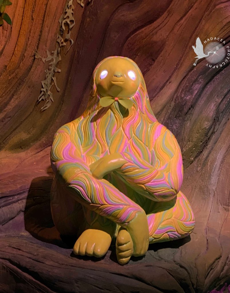 A sloth statute in soft, multi-colored tones sits in a nook. His eyes shine white lights.