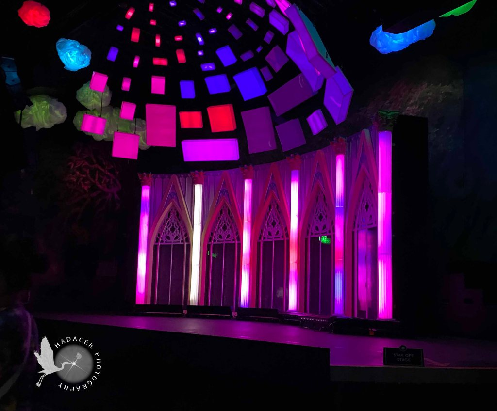 Lights above the stage are in multicolored rectangles. The stage backdrop looks like a row of glass windows, each coming to an elaborate peak.